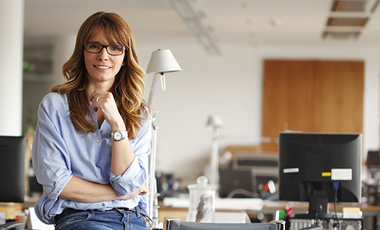female employee sitting on edge of desk